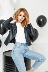 Alonesdj Beautiful young blonde girl in a black leather jacket and jeans is posing near a black metal barrel and balloons